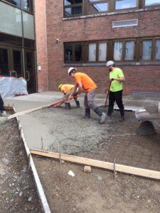 Placing concrete sidewalk at GHS