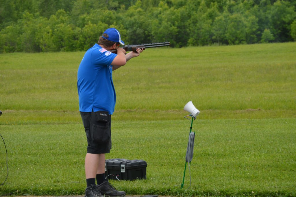 With his back to the camera, Connor Wight shoots trap on a green lawn.