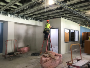 A construction worker installs drywall in the high school library on Aug. 6, 2021.